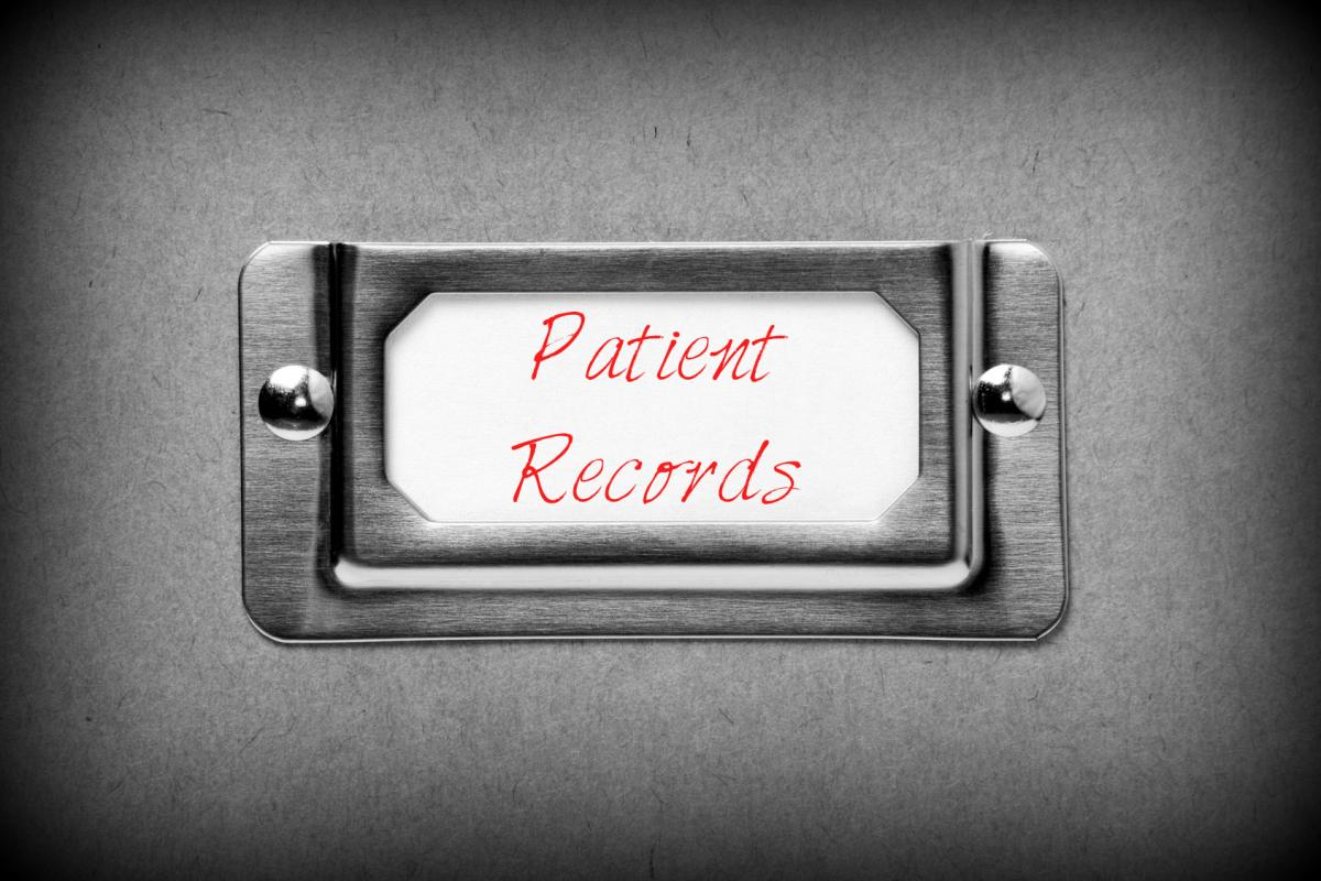 "Filing Cabinet close-up with the words ""Patient Records"" in red on the label"