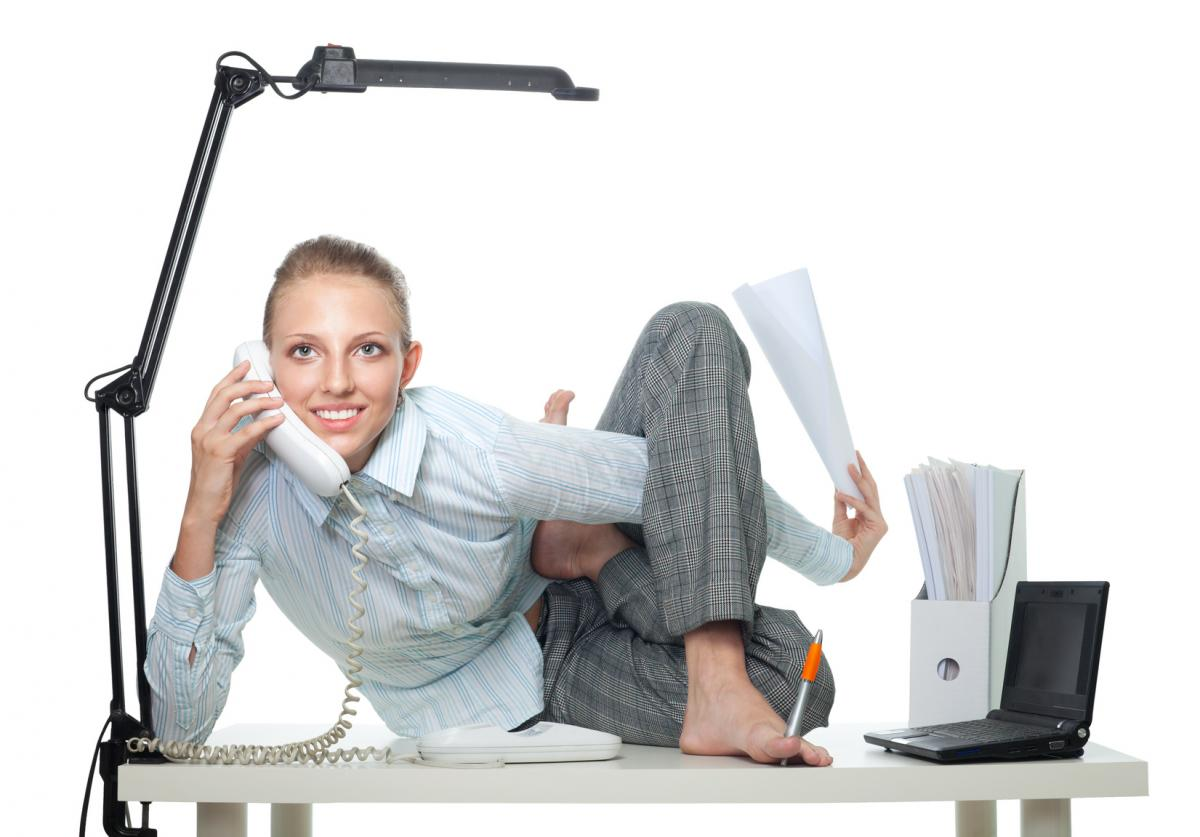 Woman doing Yoga on her desk while on the phone